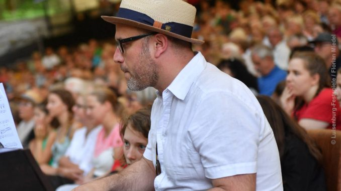 Komponist Philipp Riedel sitz an einem Klavier, im Hintergrund das Publikum